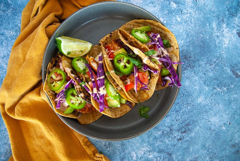 4 Fish Tacos on a dinner Plate with a blue background