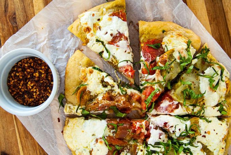 Tomato Burrata and Bail pizza cut into slices