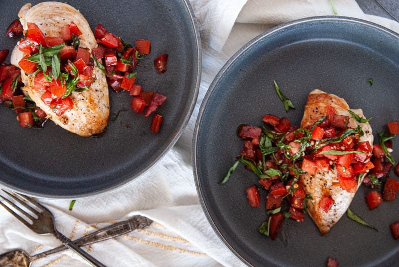 Close up of Two plates of chicken breast with bruschetta on top