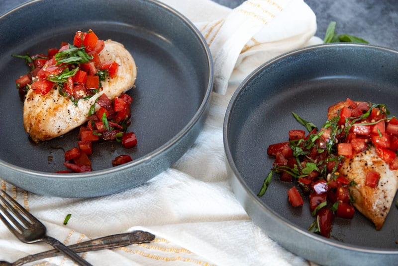 Two Grilled Chicken Breast with Bruschetta and Basil on top