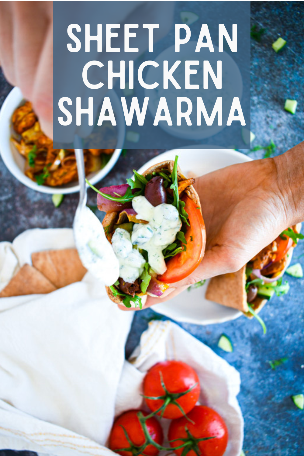 Overhead shot of sheet pan chicken shawarma topped with creamy tzatiki