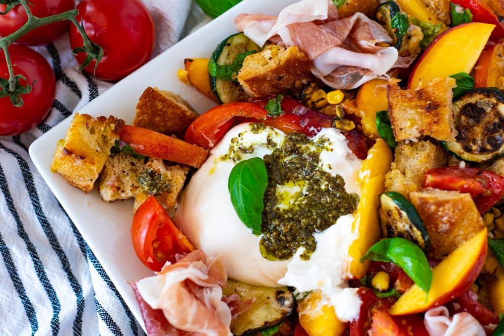 Close up of Pesto Smothered Burrata on top of a Summer Panzanella Salad with homemade croutons
