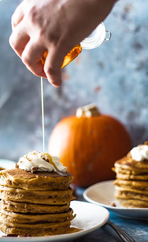 syrup getting drizzled onto whole wheat pumpkin pancakes, the best thanksgiving breakfast ideas